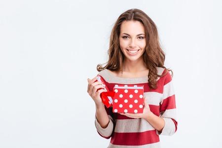 Portret van een glimlachende leuke vrouw opening geschenkdoos en kijken naar camera geïsoleerd op een witte achtergrond