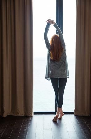 estiramiento: Vista trasera de la atractiva joven delgado con hermoso pelo largo y rojo de pie descalzo y estiramiento en la ventana grande