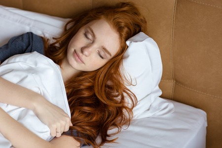 woman laying: Portrait of a young redhead woman sleeping in the bed at home Stock Photo