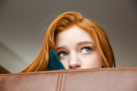 peeping: Unconfident shy redhead girl peeping over brown leather sofa and looking away