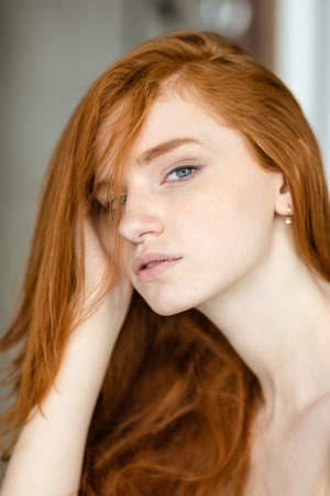 attractiveness: Portrait of a beautiful redhead woman looking at camera Stock Photo