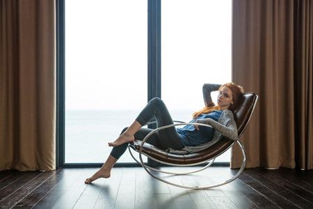 Porträt einer schönen rothaarige Frau sitzt auf Schaukelstuhl zu Hause Standard-Bild - 48788771