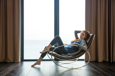 Portrait of a beautiful redhead woman sitting on rocking chair at home Banco de Imagens
