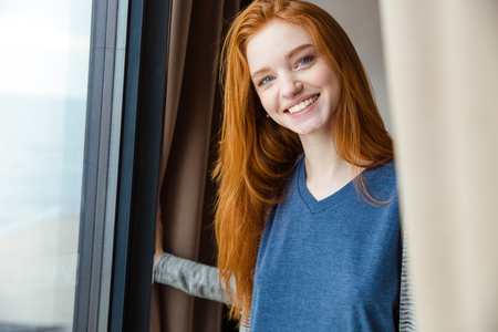 Cheerful content pretty girl with long red hair looking camera and smiling