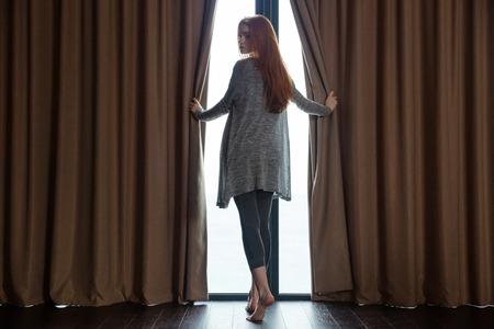 편안한 아름다운 빨간 머리 젊은 여자, 커튼을 여는 창 앞에 맨발로 서 다시 찾고 스톡 콘텐츠