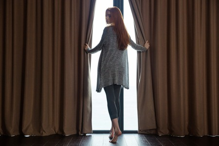 Ontspannen mooie roodharige jonge vrouw die de gordijnen opent, blote voeten voor het raam staan en terugkijkt