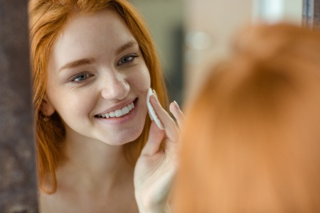 wadding: Portrait of a smiling redhair woman with wadding looking at her reflection in mirror
