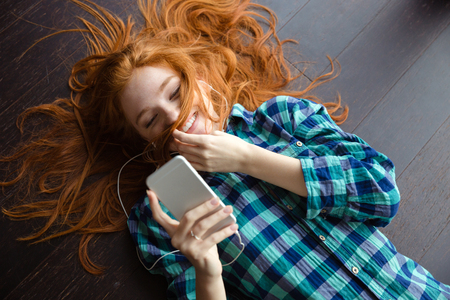 Funny amusing redhead girl in checkered shirt playing with her hair and listening to music