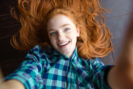 self image: Close up portrait of cheerful beautiful redhead young woman in plaid shirt making self image lying on the floor