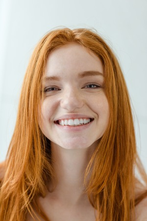 Portrait of a charmig smiling redhead woman looking at camera on gray background