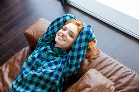 blue plaid: Positive relaxed redhead girl in blue plaid shirt resting on brown leather couch