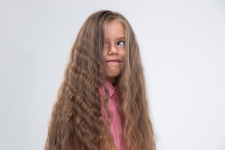 horseplay: Portrait of a little girl with long hair making silly face isolated on a white background