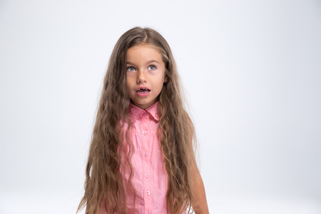 stumped: Portrait of amazed little girl looking away at copyspace isolated on a white background Stock Photo