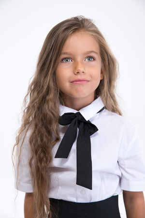 Portrait of a little school girl standing isolated on a white background and looking away Stock Photo