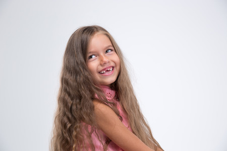 little: Portrait of a laughing little girl looking away isolated on a white background Stock Photo