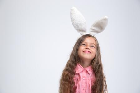 oido: Retrato de una niña feliz con orejas de conejo mirando copyspace aislado en un fondo blanco