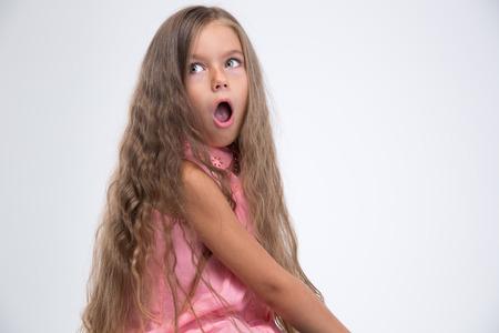 boca abierta: Retrato de la niña sorprendida mirando fuera de casa aislada sobre un fondo blanco