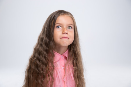horseplay: Portrait of a cute little girl making silly face isolated on a white background