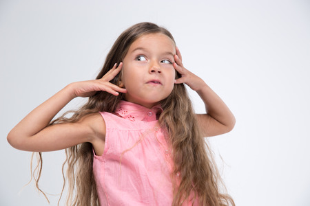 horseplay: Portrait of a little girl making silly face isolated on a white background