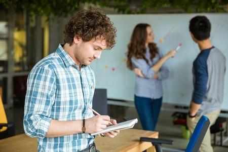 通信: ノートに書くと、パートナーとのチームで働く市松模様のシャツに物思いにふける中オスを集中してください。