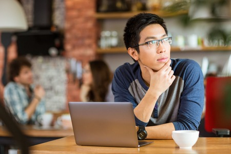 Thoughtful handsome young asian man in glasses sitting with laptop in cafe and looking away Banque d'images
