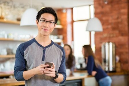 Handsome smart young asian man in glasses standing in cafe and using mobile phone