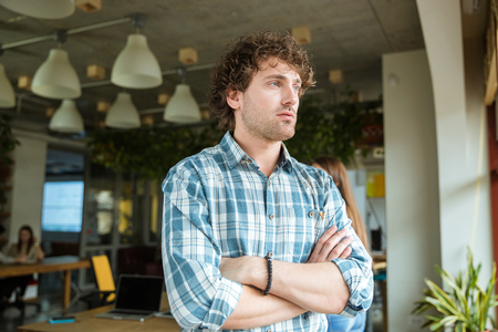Thoughtful handsome young curly man in plaid shirt standing in office with folded hands Stock Photo