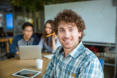 a study: Handsome positive young curly man in plaid shirt sitting and studying together with friends