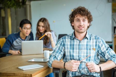 estudiando: alegre atractivo var�n joven rizado en camisa de cuadros con el estudio de los estudiantes en el aula