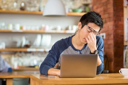 perezoso: Cansado agotado var�n asi�tico joven que trabaja con la computadora port�til en el caf�