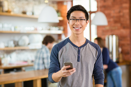 Young happy smiling attractive asian boy in glases using smarphone in cafe