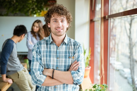 Attractive positive curly young male in checkered shirt posing in office with folded hands standing near the window