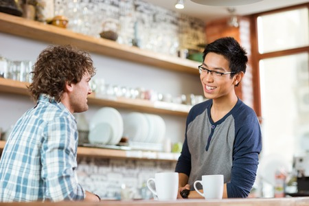 handsome student: Two young handsome men drinking tea and talking in cafe Stock Photo