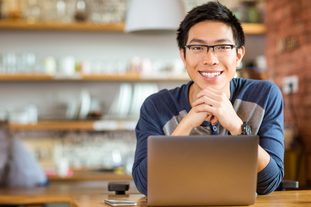 estudiando: Retrato del varón asiático positivo en vasos con el portátil en el café Foto de archivo