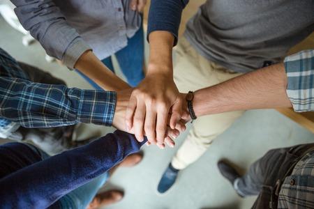 comunidad: Vista desde arriba de la gente que une las manos como símbolo de la asociación