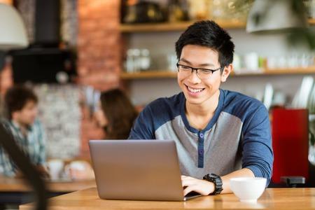 using the computer: Feliz alegre joven varón asiático con gafas sonriendo y usando la computadora portátil en el café Foto de archivo