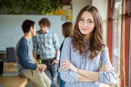 confianza: Sonriente atractiva mujer rizada joven de pie cerca de la ventana con los brazos cruzados y con sus colegas en el fondo
