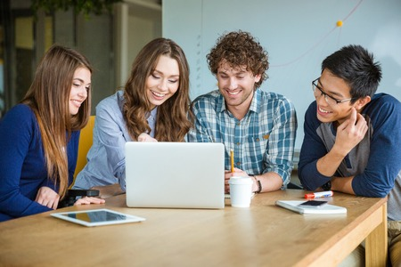 Group of positive cheerful students using laptop and doing homework together in classroom Stock Photo