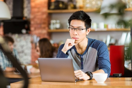 univercity: Concentrated pensive young handsome asian man in glasses sitting in cafe, thinking and using laptop