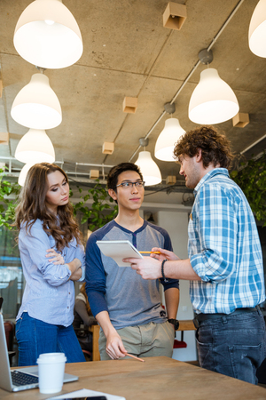 ambitious: Young ambitious team of people working on new project together in the office Stock Photo