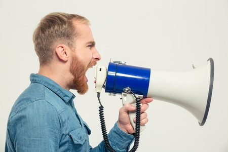 man yelling: Side view portrait of a casual man yelling into megaphone isolated on a white background Stock Photo