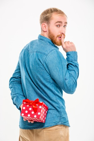 gift behind back: Handsome young bearded man hiding gift behind back and gesturing silence over white background
