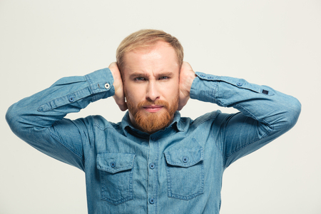 hands over ears: Young angry frustrated handsome bearded man closed ears by hands over white background