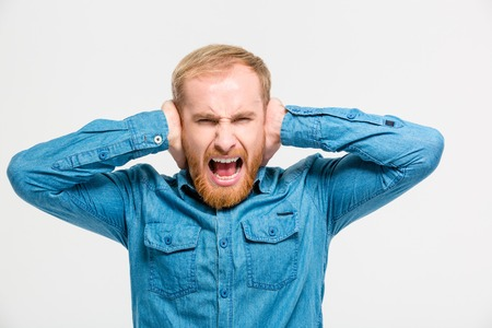 hands over ears: Mad hysterical young man with beard closed ears by hands and screaming isolated over white background
