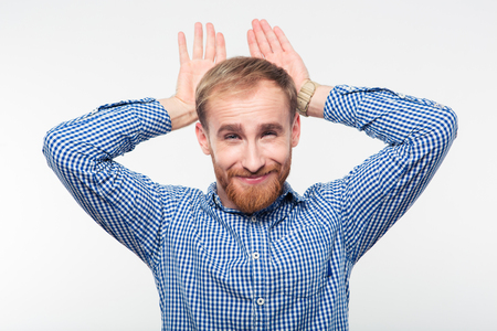 hands over ears: Portrait of a funny casual man showing rabbit geture over his head isolated on a white background