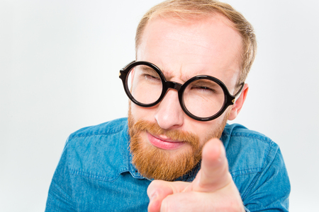 funny bearded man: Portrait of suspicious young bearded man in funny round glasses pointing on you isolated over white background Stock Photo