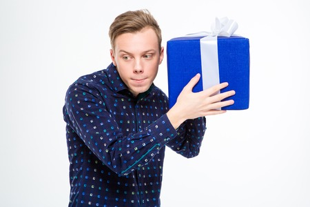 birthday presents: Amusing curious blond man in plaid shirt  trying to listen something inside present box over white background