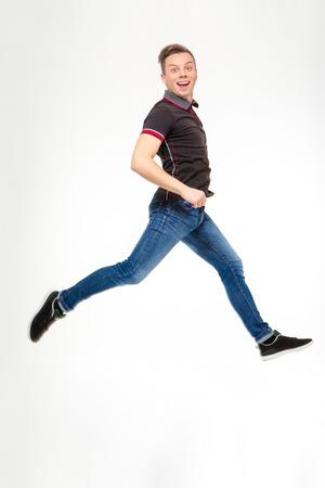 persona saltando: Foto integral del hombre joven feliz excitado en negro camiseta y pantalones vaqueros que saltan y funcionamiento aislado en el fondo blanco