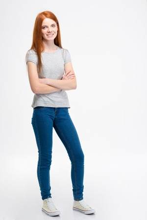 look pleased: Young beautiful woman with long red hair standing with crossed arms over white background Stock Photo