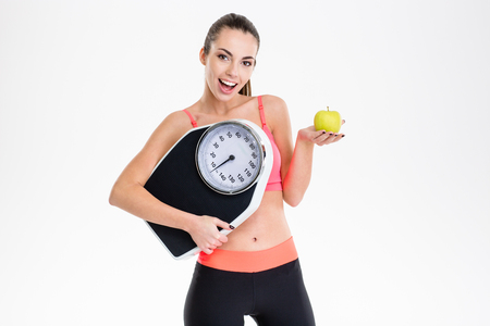 tracksuit: Excited positive fitness girl in tracksuit holding weighing scale and apple over white background